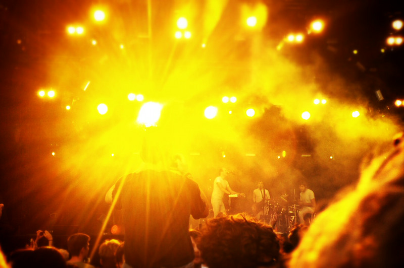 Caribou performing under a yellow spotlight at the Pitch Festival in Amsterdam.