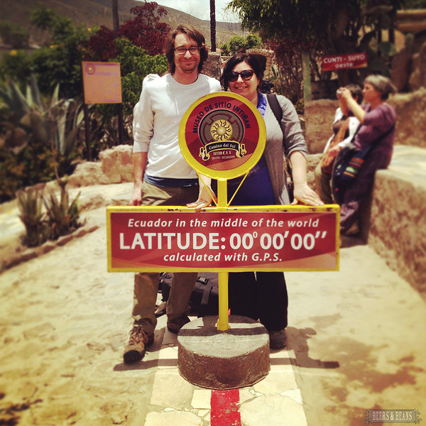 Two travelers pose in front of a 0 Latitude sign during an equator tour.