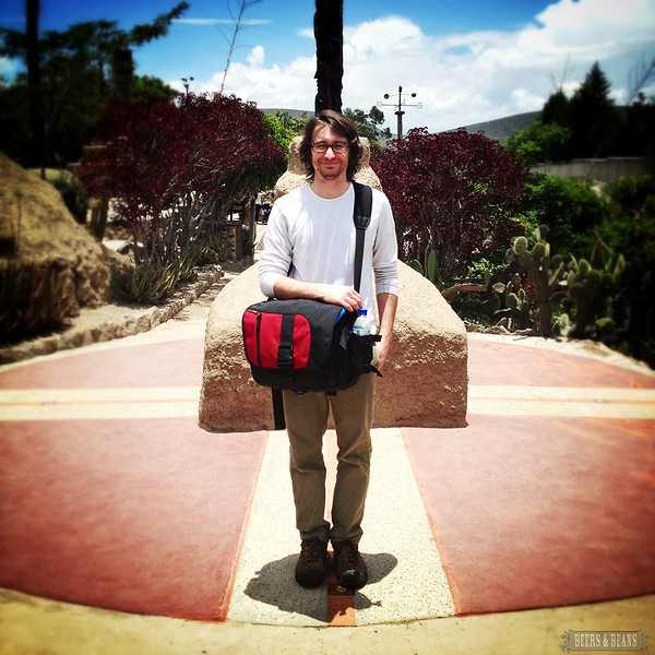A young man stands with a Tom Bihn in Ecuador during an Equator tour.